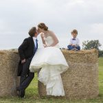 Bride and Groom kissing on Hay Bales
