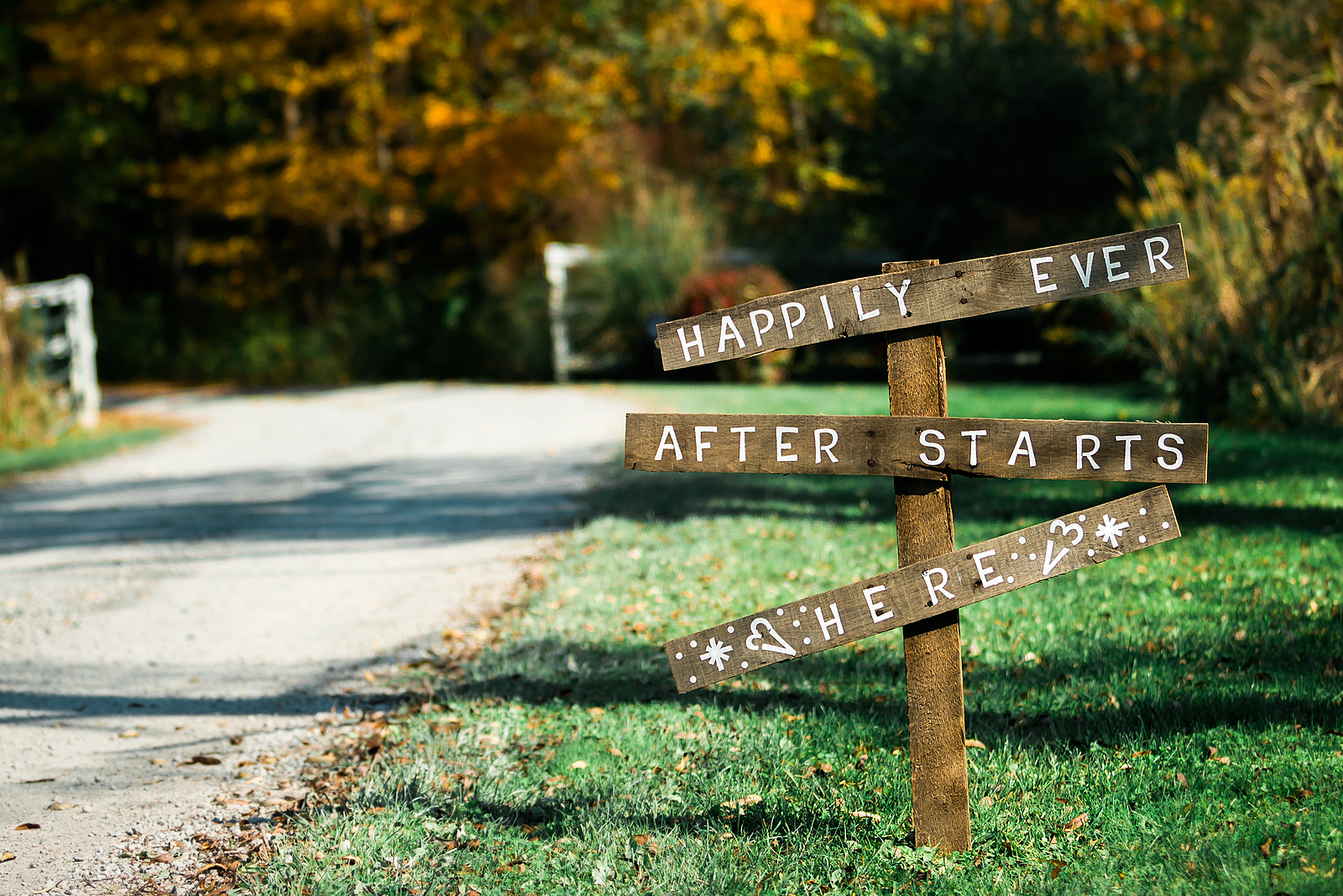 Wedding sign says happily ever after starts here and a road leads to the wedding venue.