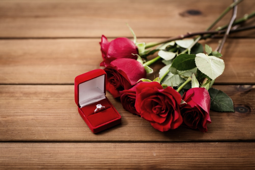 love, proposal, valentines day and holidays concept - close up of gift box with diamond engagement ring and red roses on wood (vintage effect)