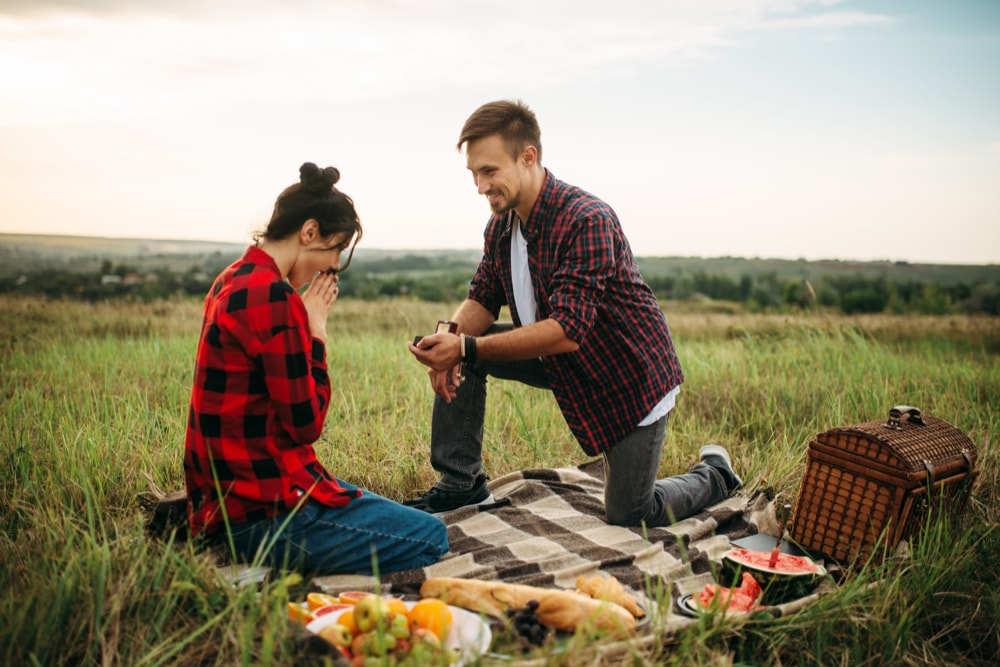 Man makes a marriage proposal on romantic picnic in summer field. Junket of man and woman, happy moments