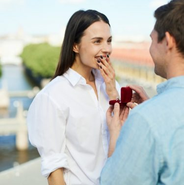 Surprised and happy girl keeping hand by her mouth while looking at boyfriend making her proposal