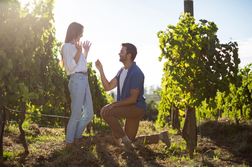 Young man proposing girlfriend at vineyard