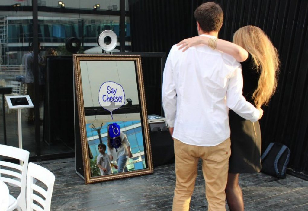 couple standing in front of a magic photo booth